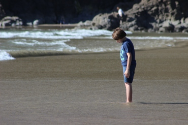 EB watching his feet sink in the sand